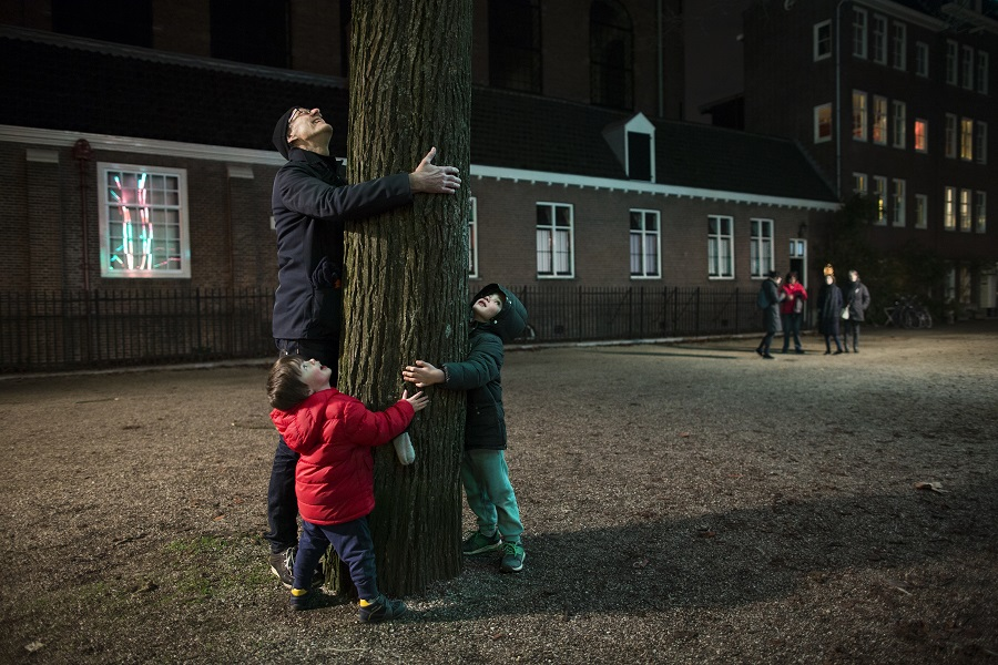 People hugging tree at Amsterdam Light Festival