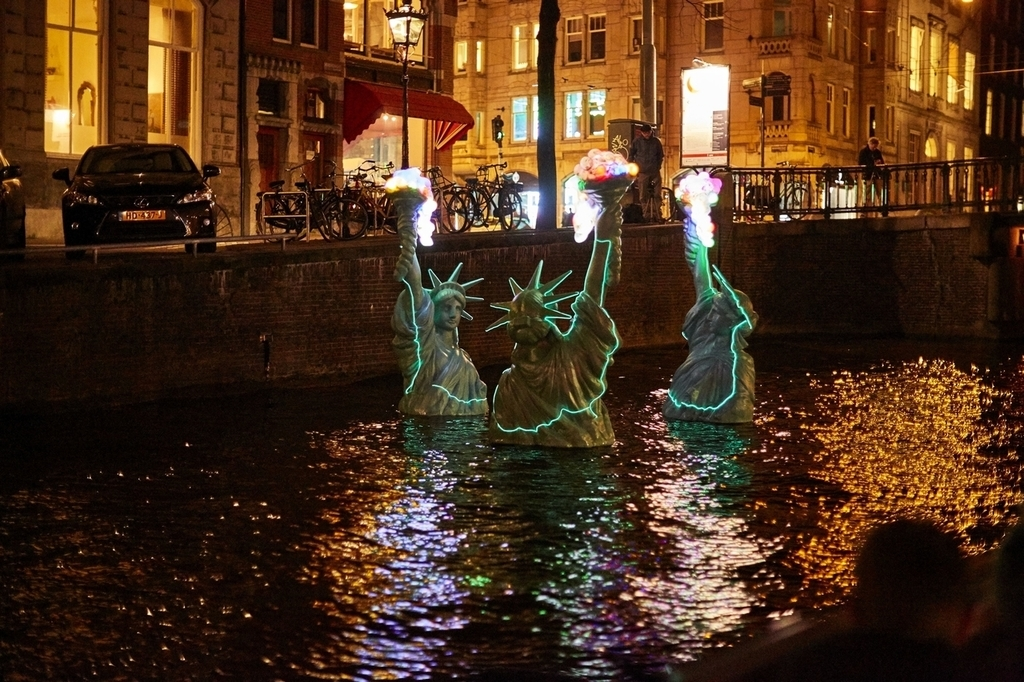 Statues of Liberty in the water of a canal during Amsterdam Light Festival create the artwork Freedom as a Valuable Friend by Erik Sok